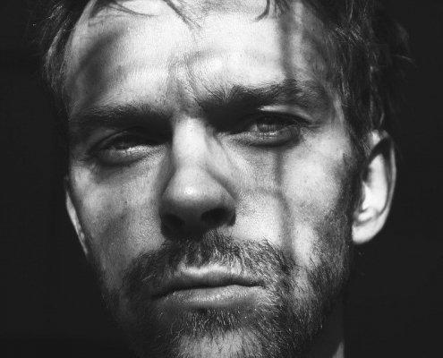 visage d'un homme avec un regard fixe, le tout en noir et blanc et très contrasté