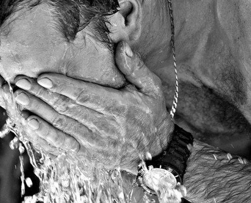 homme qui se rince le visage avec de l'eau