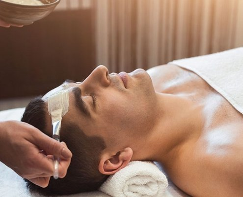 homme allongé sur table de soin recevant un soin du visage appliqué avec un pinceau par esthéticienne