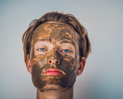 jeune homme blond avec un masque nourrissant brun sur le visage