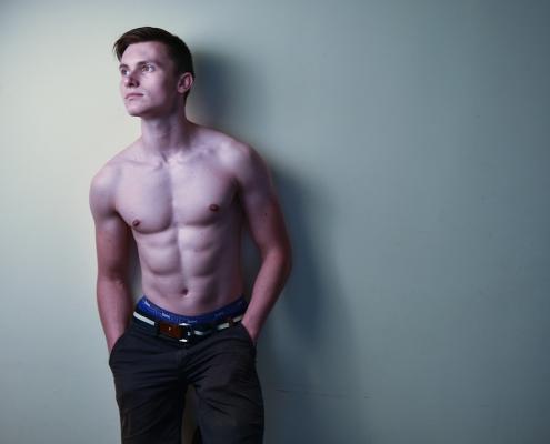 Homme torse nu qui s'appuie sur un mur blanc