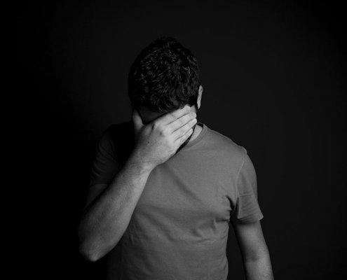 homme debout avec la main sur le visage baissé pour se cacher