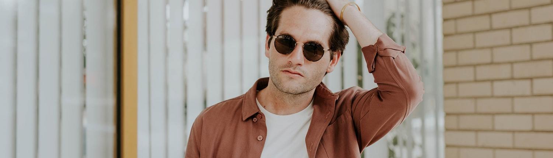 Homme avec des lunettes de soleil se passant la main dans ses cheveux