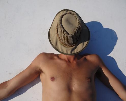 homme torse nu couché avec un chapeau sur le visage
